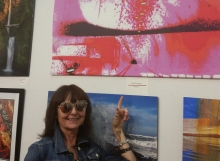 Linda Burden-Williams pointing at her award winning photo that will be on display at Eugene Mindworks